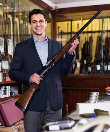 Handsome pleasant glad adult male in hunting shop with rifle in hands