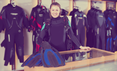 glad young woman is standing in new equipment for diving in the store.
