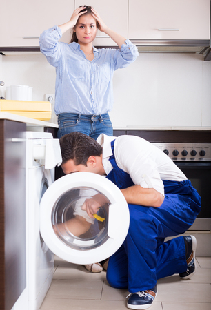 Specialist in uniform and young woman near broken washing machine at home kitchen 版權商用圖片