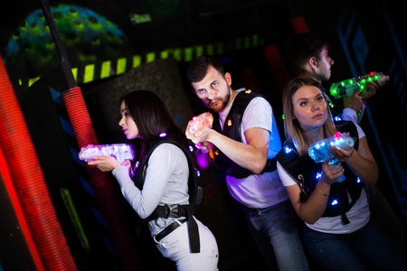Excited young people aiming laser guns at other players during lasertag game in dark room