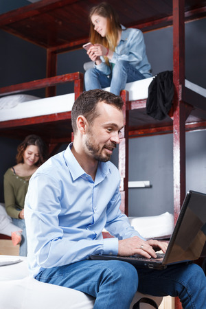 Smiling bearded man sitting with laptop on bed in cozy hostel bedroom Фото со стока - 108110042