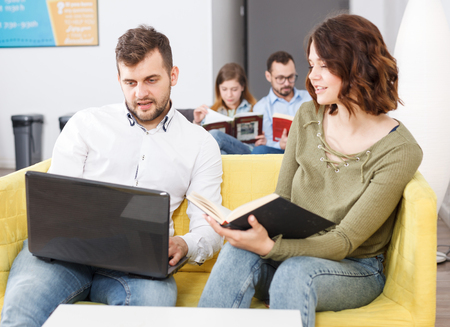 Friendly young woman and man relaxing in cozy hostel lobby, spending time with laptop and book Stock Photo