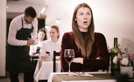 Elegant upset woman is expecting man for dinner in luxury restaurante indoor.