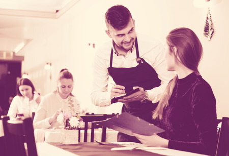 Welcoming waiter is taking order from cheerful woman in restaurante indoor.