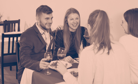 Gentleman with elegant women are having dinner in luxury restaurante indoor.