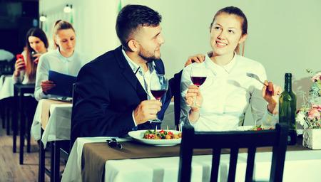 Romantic couple is having dinner in the restaurante indoor.