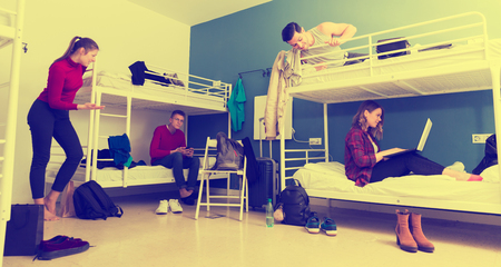 Young positive travelers interacting while resting in hostel bedroom Stock Photo