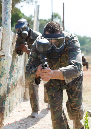 Paintball player in camouflage and mask aiming with gun in shootout outdoors