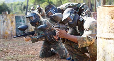 Diligent positive   paintball players aiming and shooting with guns at opposing team outdoors Stock Photo