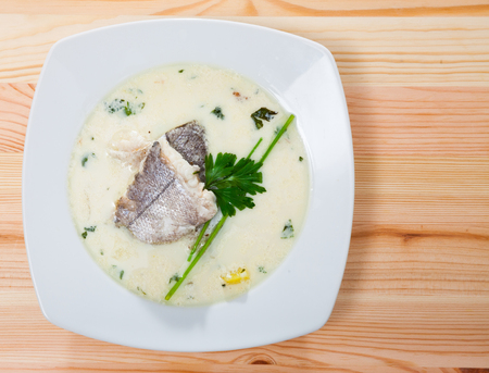 Top view of Scottish soup with smoked haddock, potatoes and onions (Cullen skink) served in white plate with greens on wooden background Stock Photo