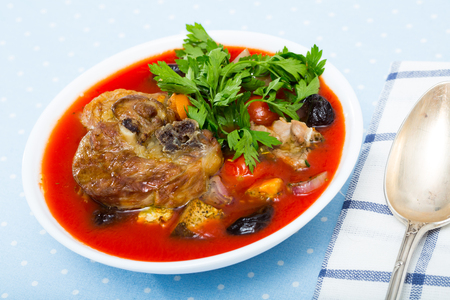 Spicy tomato soup with lamb, prunes and dried apricots served in white bowl with greens