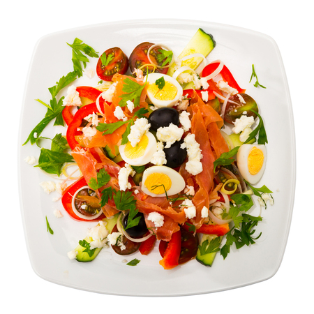 Top view of colorful Bulgarian shepherds salad with fresh vegetables and greens, quail eggs, ham and soft cheese on blue tablecloth. Isolated over white background Stockfoto