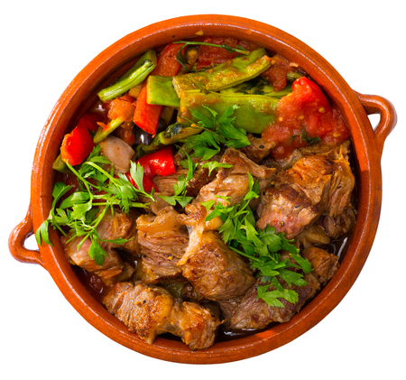 Top view of Bulgarian dish Guvech - baked meat with assorted vegetables and greens traditionally served in earthenware pot.  Isolated over white background Reklamní fotografie - 108239215