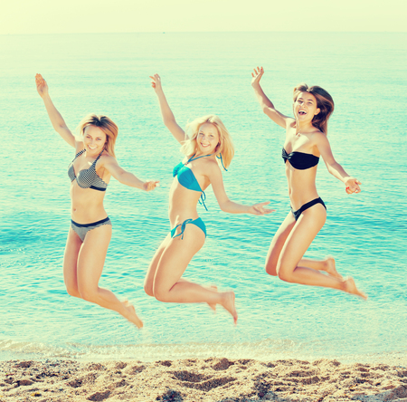 Portrait of three cheerful young women in swimsuits hopping together on a beach. Focus on right person