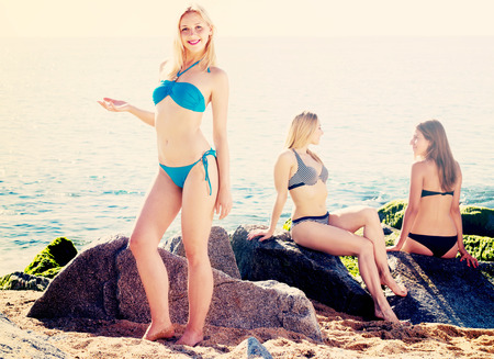 Positive girl in bikini standing on beach and smiling while her friends resting