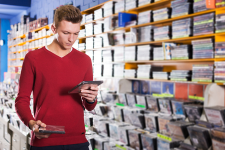Handsome focused young guy looking on box of DVD movie during shopping in CD shop Stock Photo