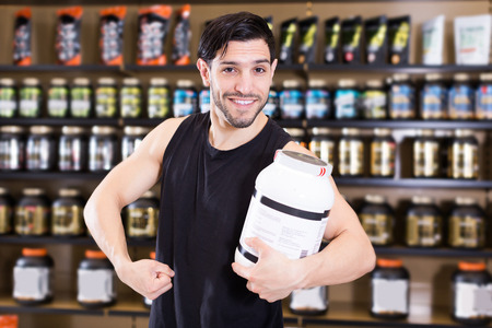 smiling active muscular man showing his biceps and holding pot of  sport nutrition in shop