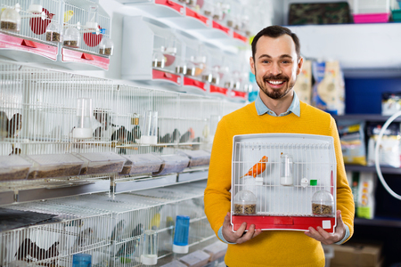 Young male customer boasting his purchase of canary bird in pet shop Stock Photo