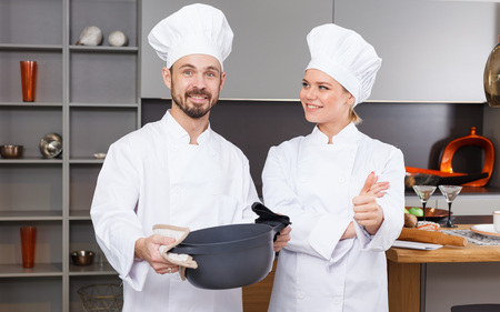 Two confident personal chefs in white coats standing in modern interior of private kitchen Zdjęcie Seryjne
