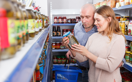 Positive family couple with basket buying canned goods in the food store