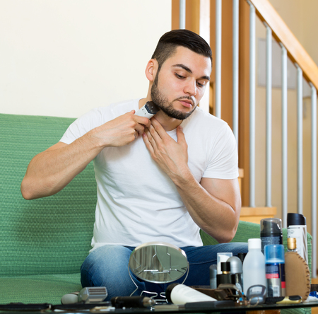 Young guy shaving by trimmer at home