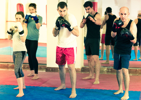 Portrait of young cheerful females and adult males training in boxing gloves