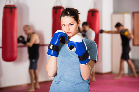Portrait of young cheerful female sportswear training in colored boxing gloves