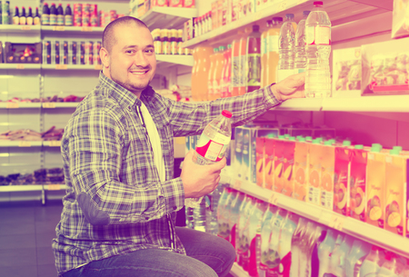Portrait of smiling man in plaid shirt choosing mineral water in grocery