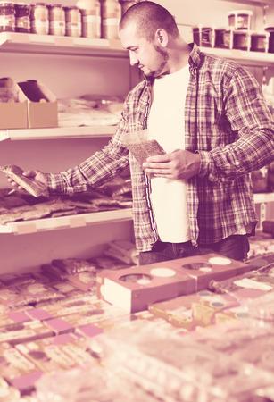 happy male customer choosing nuts and grain in average food shop