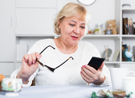 Mature woman enjoys a modern smartphone while sitting at home at a table Imagens