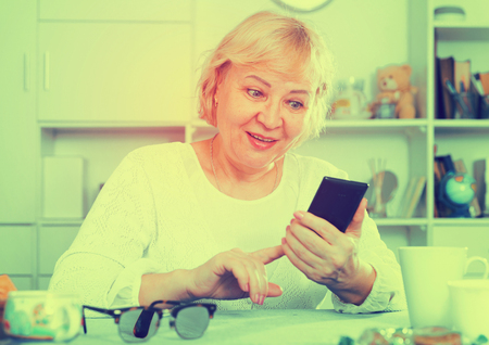 Smartphone in the hands of an interested mature woman