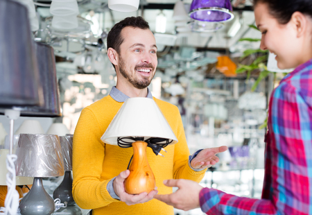 Cheerful man and girl in lighter shop choose stylish and modern lamp for house interior