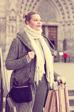 girl teenager with baggage in the historical city in scarf outdoors