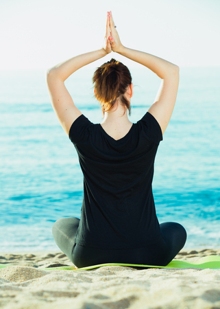 Female 20-30 years old is sitting her back and practicing meditation in black T-shirt on the beach. Imagens