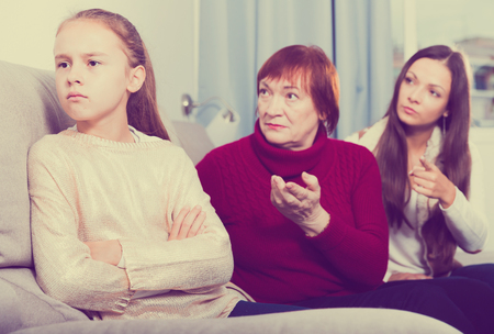 Portrait of upset little girl scolded by mother and grandma at home