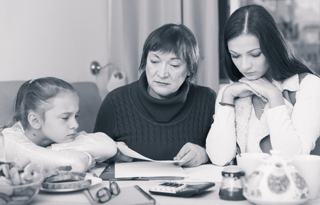 Senior lady with adult daughter and granddaughter looking worriedly at papers at home