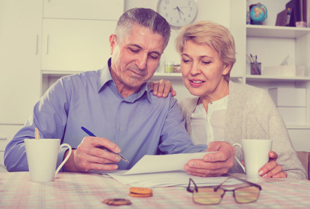 Glad  mature married couple discuss contract at home and sign important documents