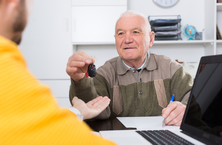 Elderly man and manager signed car purchase contract at office and hand over keys