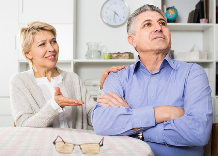 mature italian husband and wife arguing with each other and try to resolve family conflict at table