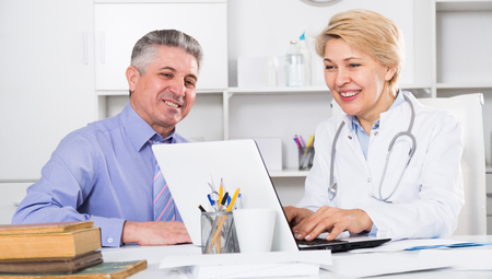 Mature man visiting doctor in clinic office for advice on health
