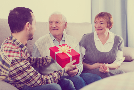 Son gives holiday gift box to elderly parents at home