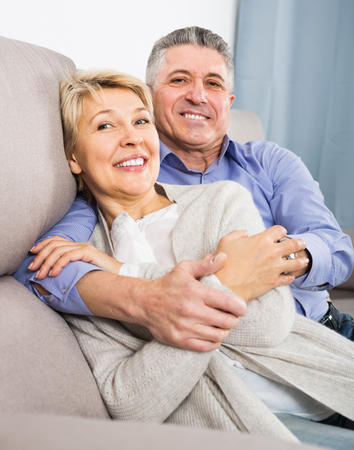 joyous mature married couple in cozy house are warmly reconciled after quarrel Archivio Fotografico