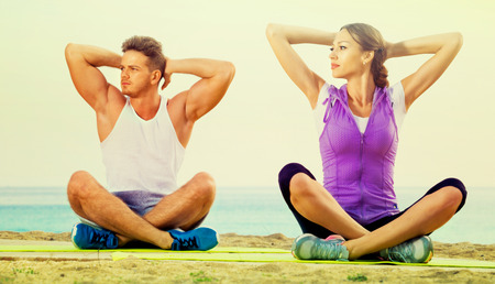 Cheerful positive woman and man sitting cross-legged do yoga poses on beach at daytime