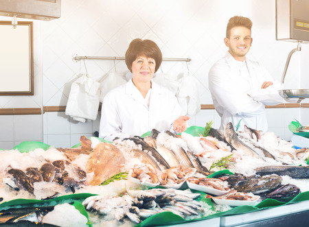 Ordinary fish and seafood store with two positive sellers indoors Stock Photo