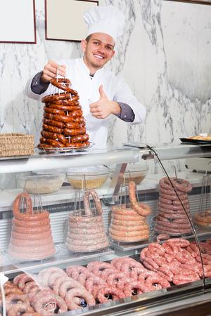 Adult ordinary man seller working at meat market Banco de Imagens