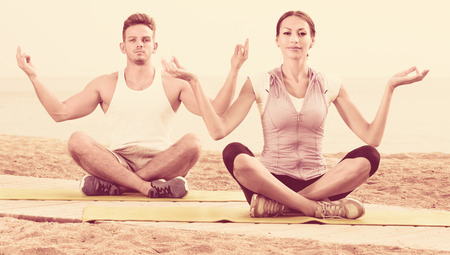 Happy friendly smiling woman and man sitting cross-legged do yoga poses on beach at daytime