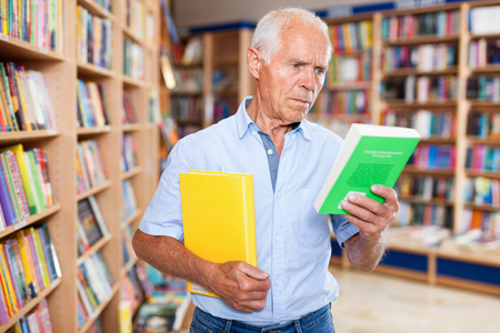 Portrait of intelligent positive friendly  older man choosing necessary books on shelves in library Stockfoto