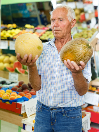Positive mature male customer searching for fresh fruits in greengrocery