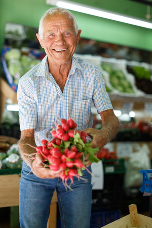 Senior man searching for fresh vegetables while shopping in greengrocery Stok Fotoğraf