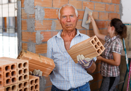 Focused elderly man working with daughter on their home renovations, installing brick wall inside Foto de archivo